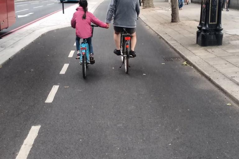 Girl holding hands with dad on cycle superhighway.jpg