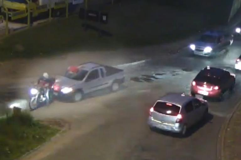 A motorcyclist attempts to stop the car with the rider's body embedded in the windcsreen