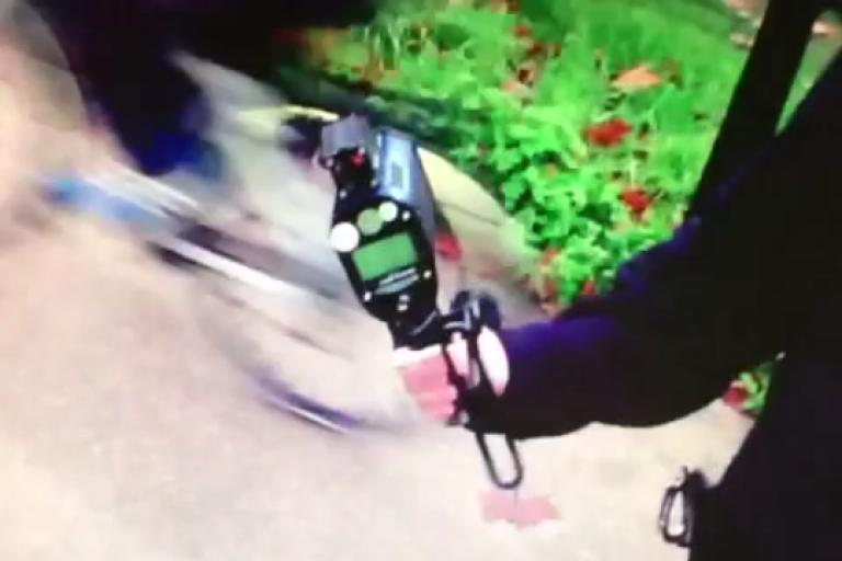 An officer shows Jeremy Vine the radar gun as other riders pass by.png