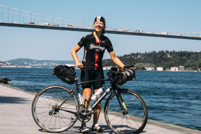 Pippa Handley poses in front of the Bosphorus Bridge after winning the women's category in the 2014 Continental Race (©Matthias Wjst:TransContinental Race)