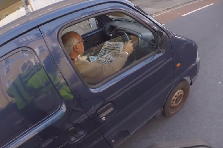 Van driver reading newspaper (image taken from YouTube).jpg